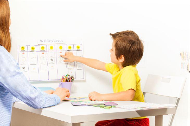 little boy learning to read a calendar