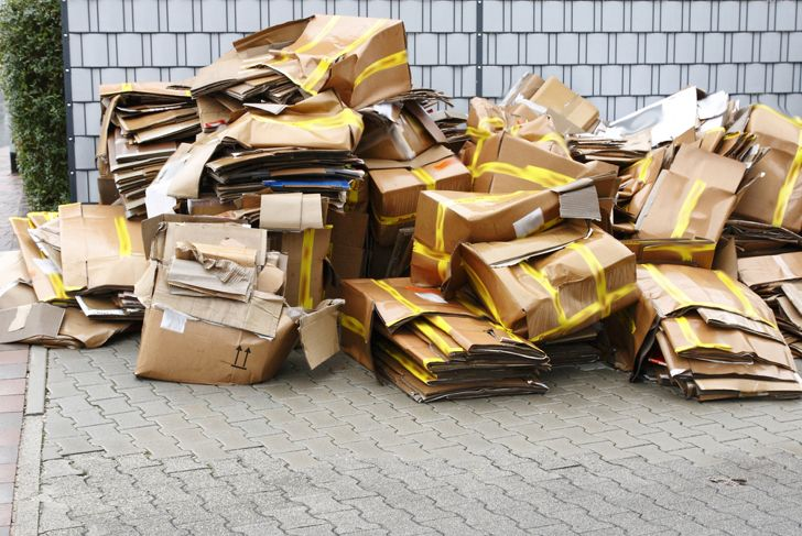 stacks of cardboard outside wet from the rain