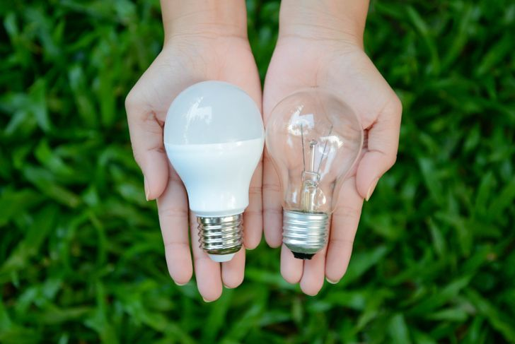 a woman holding an LED lightbulb in one hand and an incandescent in the other