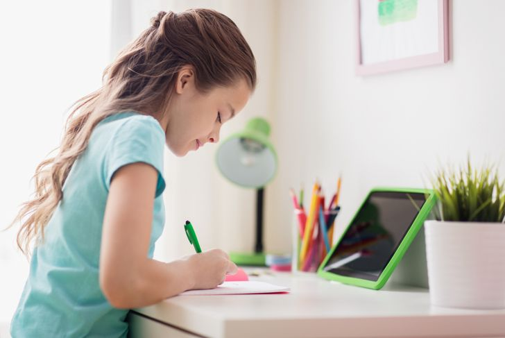 young girl doing homework at her home desk