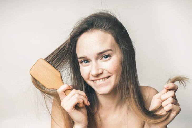 smiling woman with hairbrush and type 1A hair