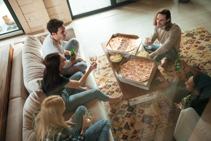 friends having pizza and wine in the living room