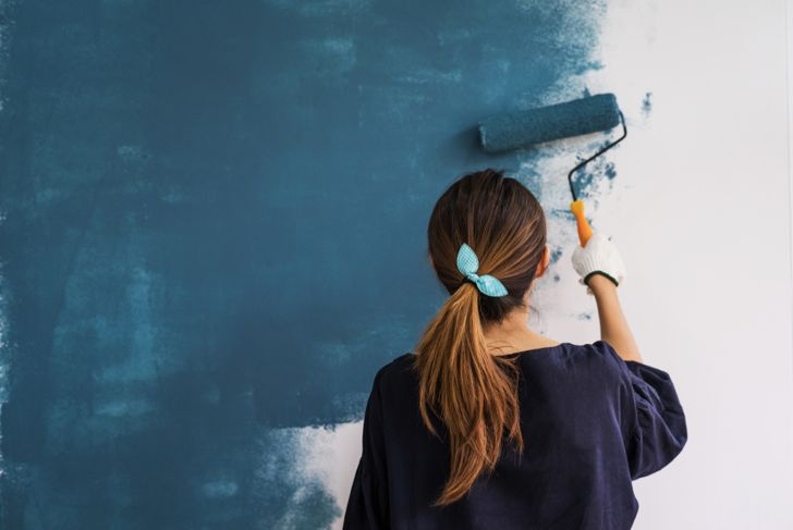 woman painting a wall a bold blue-green color