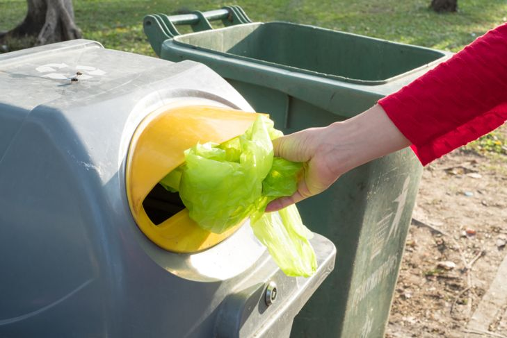 woman throwing a plastic bag in a recycling bin