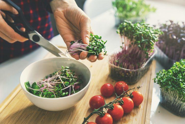 woman cutting microgreens for a salad