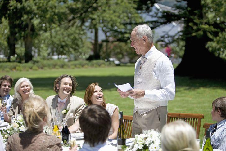 older man giving a speech at an outdoor wedding