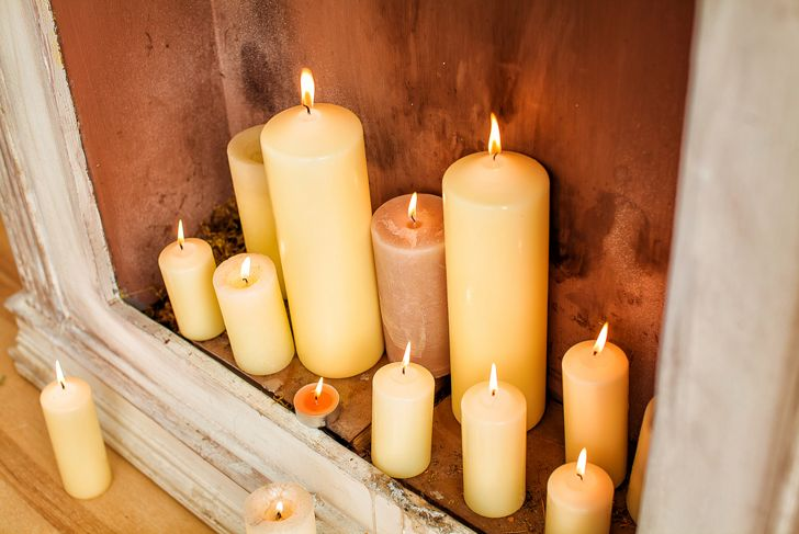 lots of pillar candles in an empty fireplace