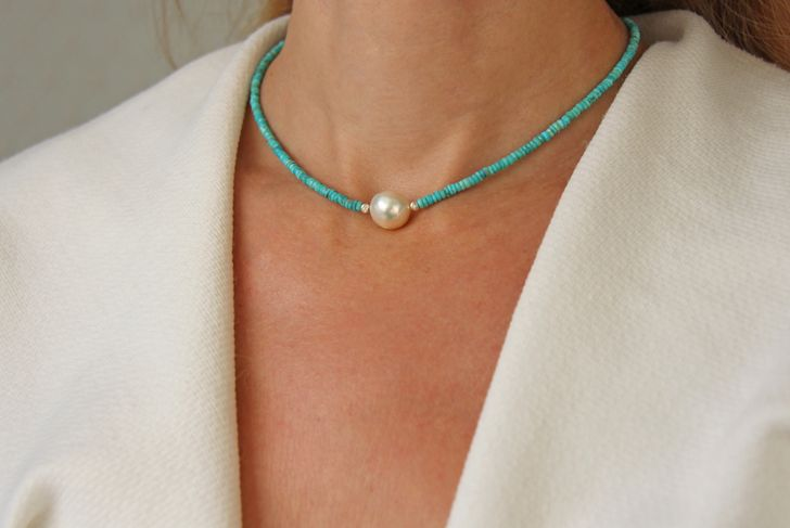 woman wearing single pearl on turquoise chain