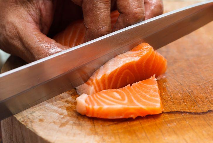 man cutting fresh salmon with a sharp knife