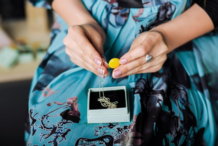 woman removing an enamel pendant on a chain from a box