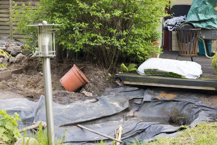 empty backyard pond with liner