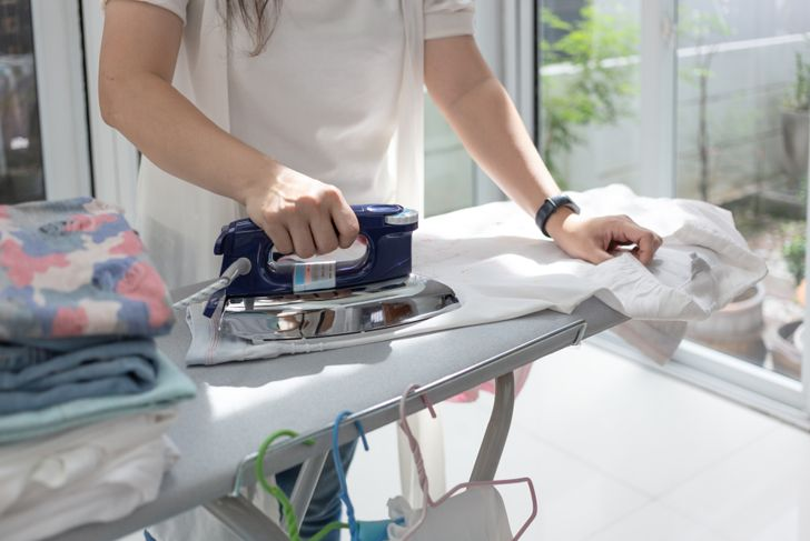 woman ironing clothes on an ironing board