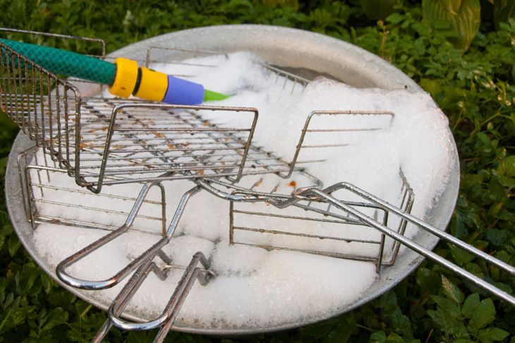 cleaning bbq grill pieces in soapy water