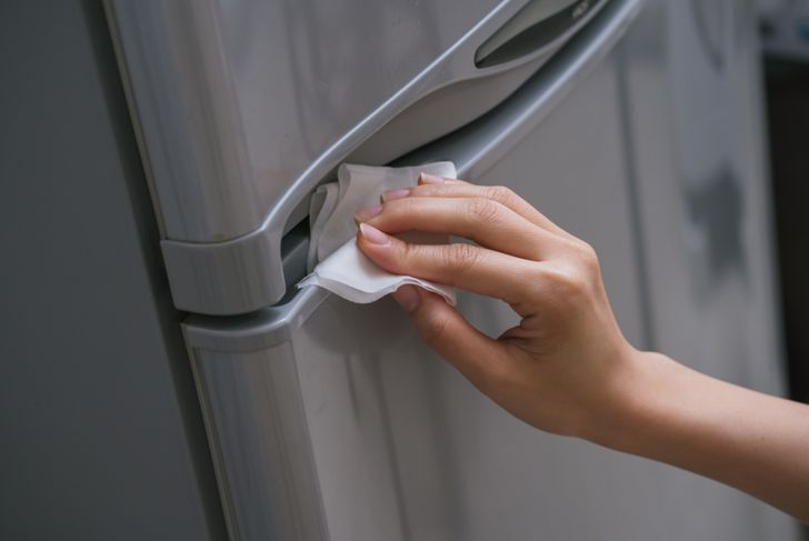 woman cleaning her stainless steel fridge