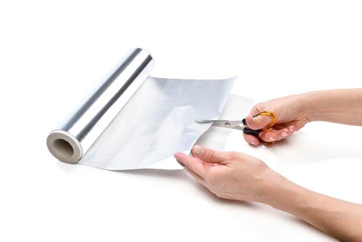 cutting aluminium foil with scissors