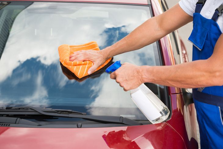 person cleaning car windshield with vinegar spray